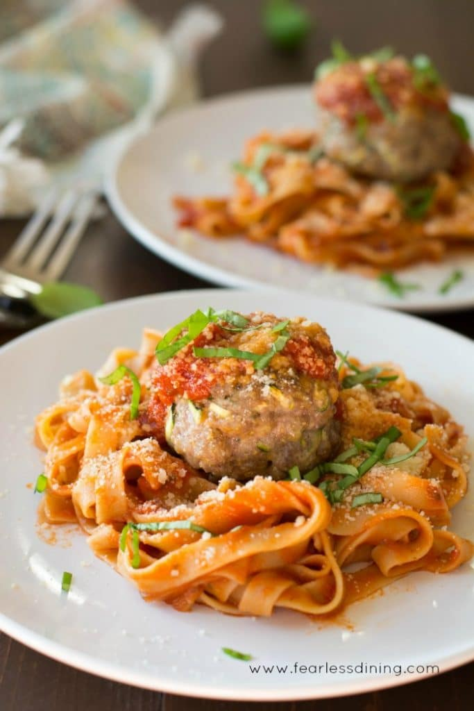Gluten Free Meatballs sitting on top of a serving of fetuccine pasta