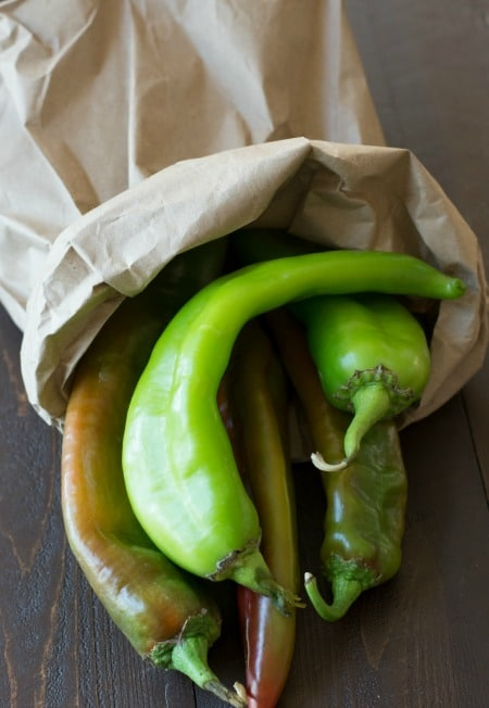 A brown paper bag with fresh hatch chiles.