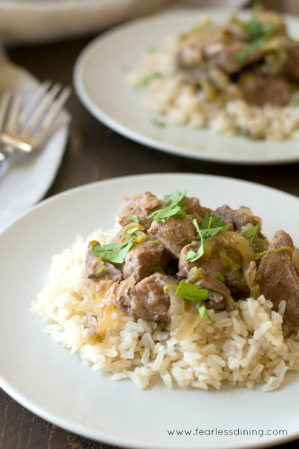 two plates of lamb stew over rice