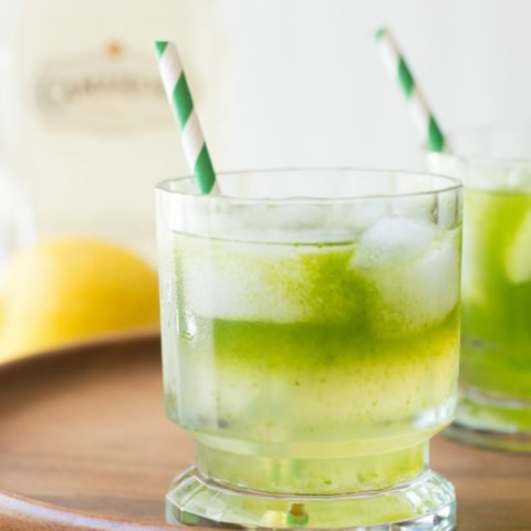 2 cocktail glasses of tequila lemonade with green striped straws sit on a wood serving platter