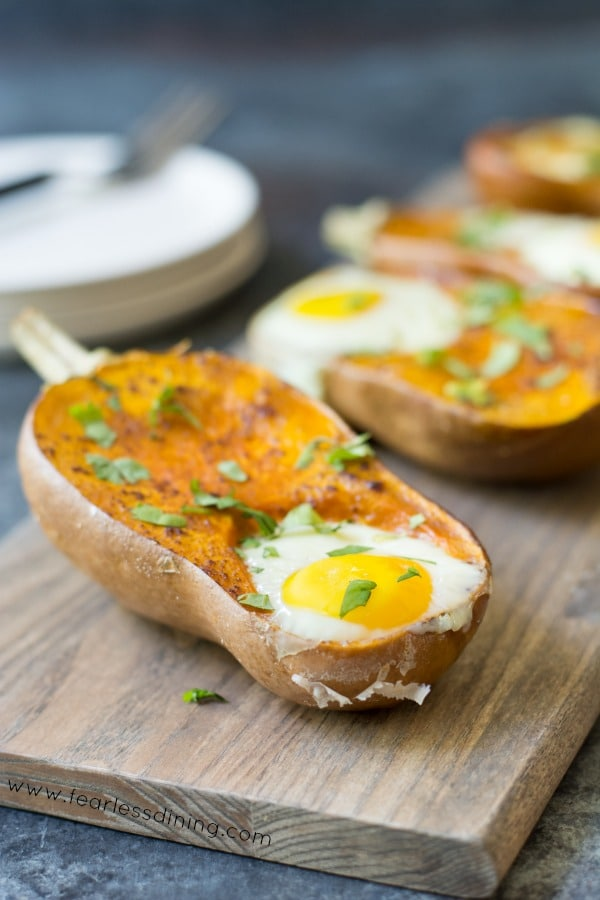 Eggs Baked in Honeynut Squash on a cutting board. Plates are in the background