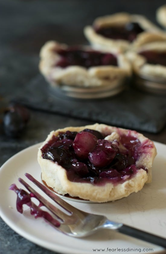 Easy Gluten Free Black Grape Mason Jar Lid Galette on a plate with a fork