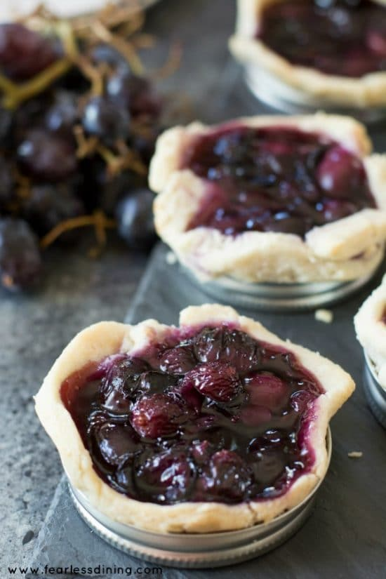 Gluten Free Mason Jar Black Grape Galettes on a serving tray. A bunch of black grapes is next to the tray.