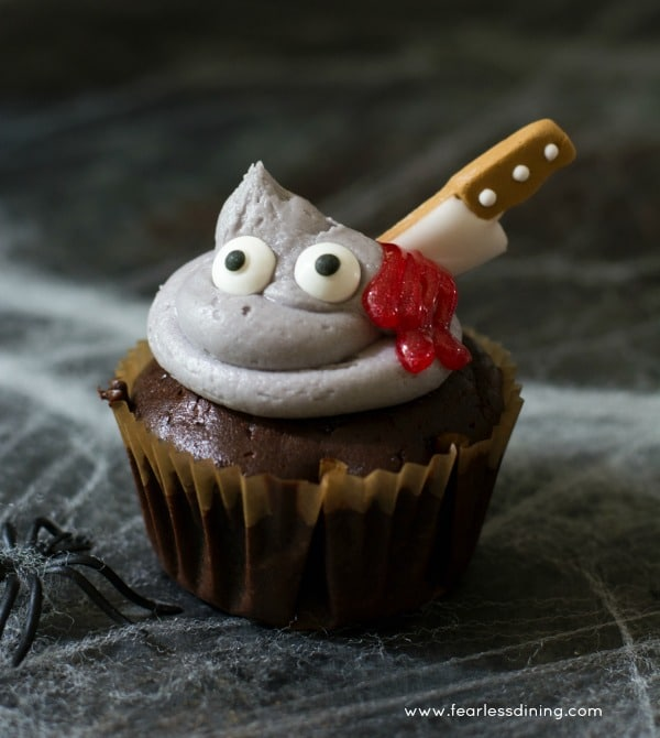 A gluten free monster chocolate cupcake with a sugar knife in its frosting head