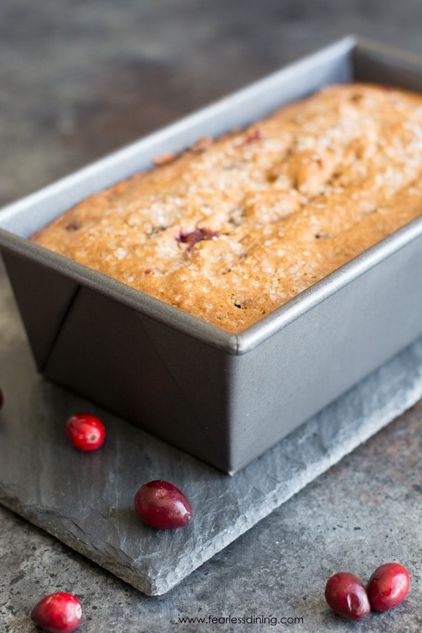 A loaf of gluten free cranberry bread in a silver bread tin. Fresh cranberries are on the counter next to it.