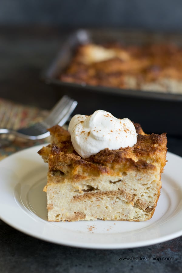 A slice of gluten free eggnog bread pudding with a dollop of whipped cream on top.