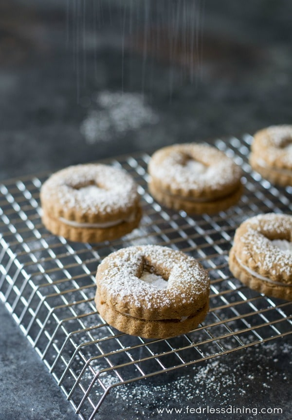 Gluten free gingerbread linzer cookies on a cooling rack with powdered sugar on top