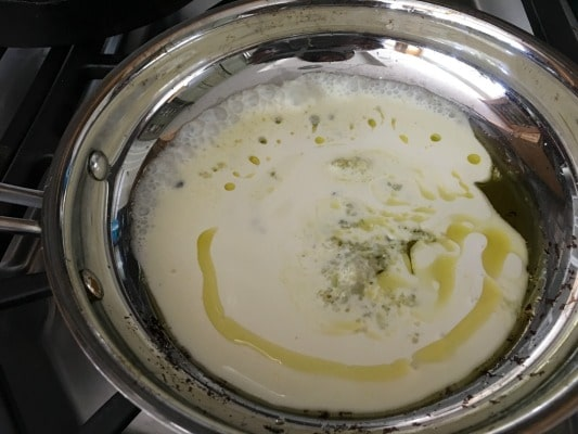 A pan with heavy cream and a little more olive oil cooking to make gluten free Alfredo sauce