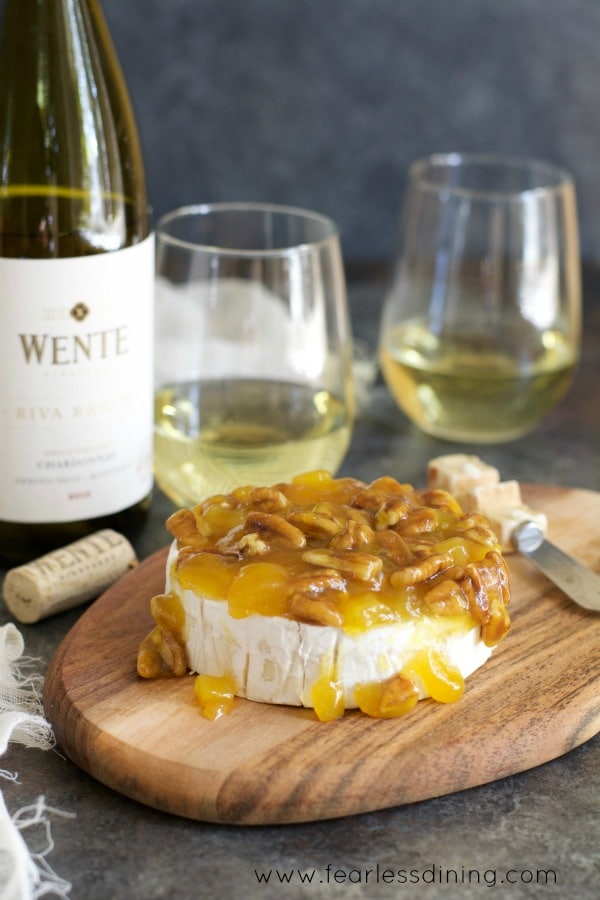 Mango Pecan sauce covered Brie with Wente Chardonnay bottle next to the cheese board