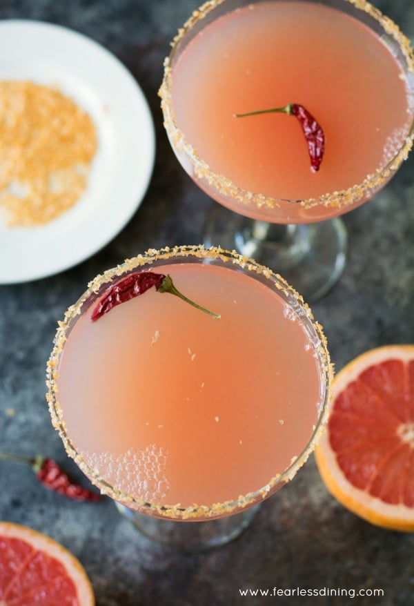 Two glasses of pink grapefruit margarita with whole red chile peppers floating in the cocktails