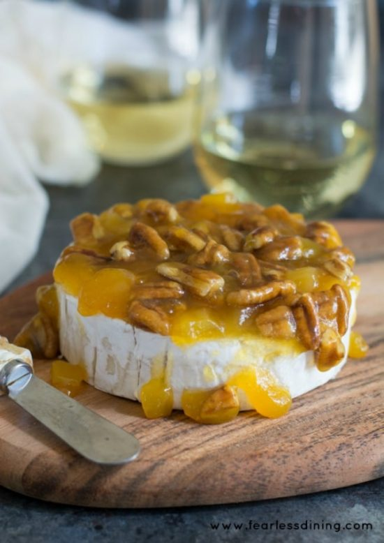 Mango and pecan topped brie sitting on a cheese board