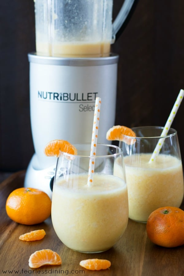 A picture of two smoothies in front of a Nutribullet blender. Slices of orange are on the table