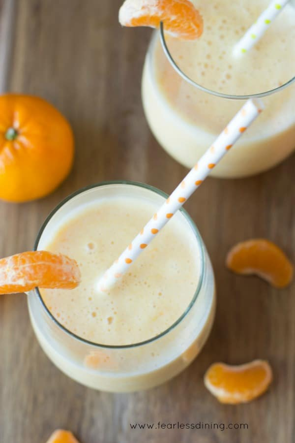 Top view of two glasses of creamsicle smoothies. Orange polka dot straws are in each glass. Pieces of orange garnish the glasses