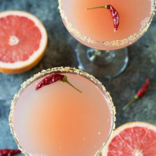 overhead photo of 2 glasses of pink grapefruit margaritas with red chile peppers floating in them.