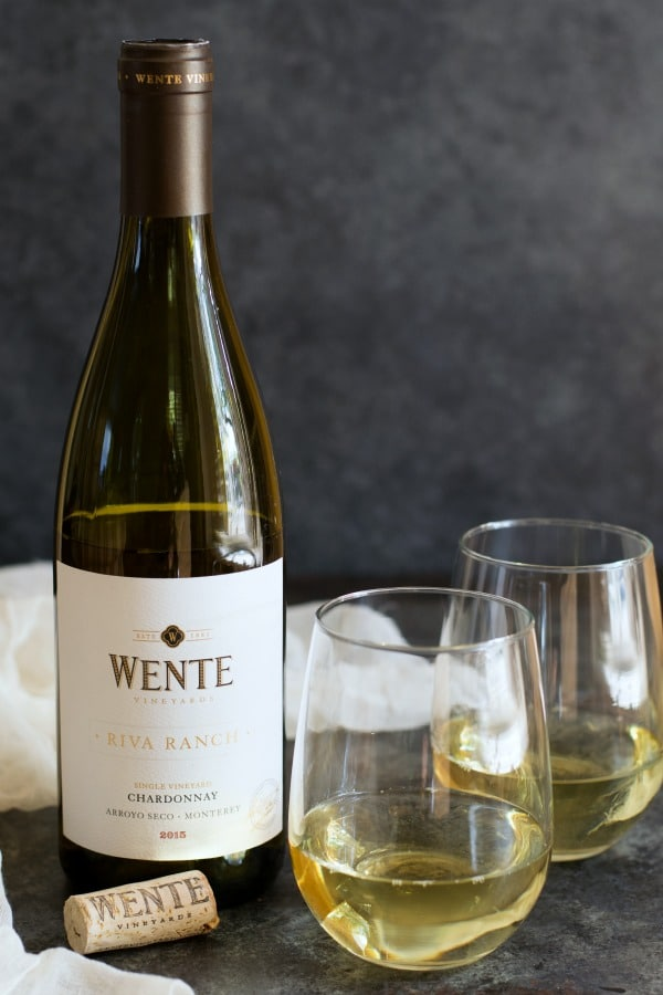 A bottle of Wente Riva Ranch Chardonnay with two wine glasses full of wine
