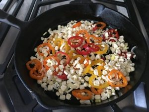Cooking corn and red peppers in a skillet