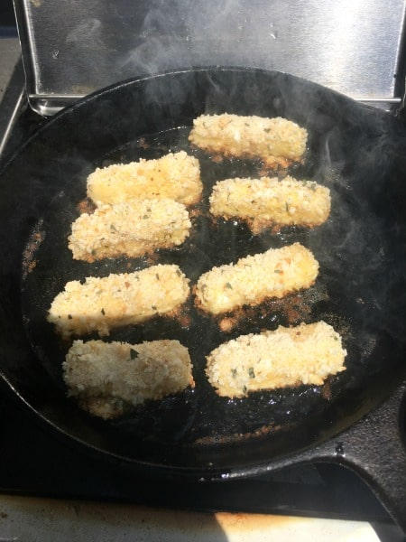 Frying cheese sticks in hot oil in a cast iron skillet