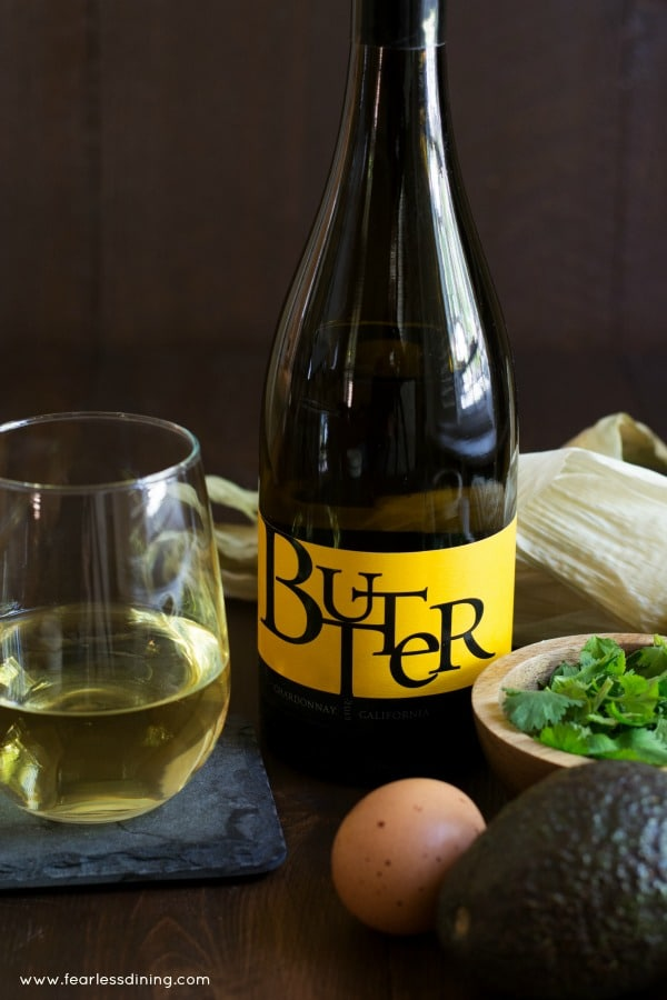 A bottle of JaM Cellars Butter Chardonnay with a wine glass and recipe ingredients.