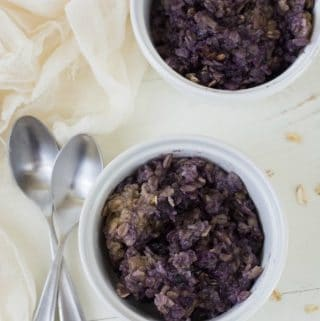 overhead photo of 2 bowls of baked blueberry oatmeal, with spoons next to the bowls
