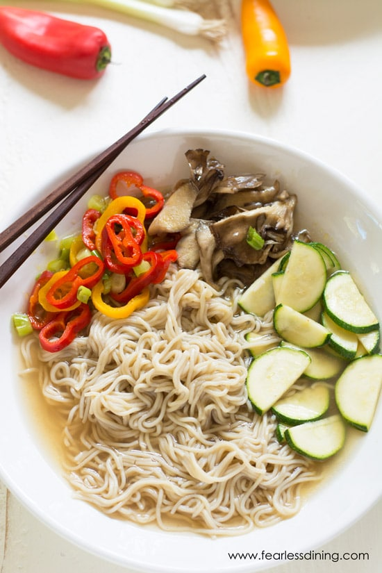 A bowl of ramen soup with peppers, zucchini and mushrooms. Chopsticks are sitting on the rim of the bowl.