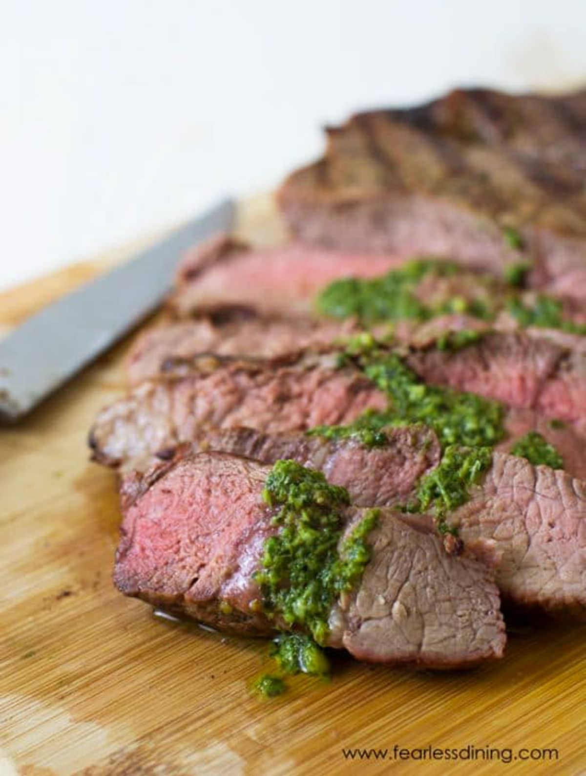 sliced NY strip steak topped with basil garlic sauce