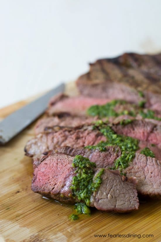 New York Sirloin sliced on a cutting board with a basil sauce on top.