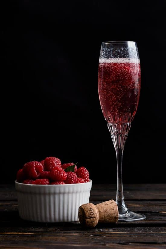 Rose French Cocktail with a bowl of raspberries next to it.