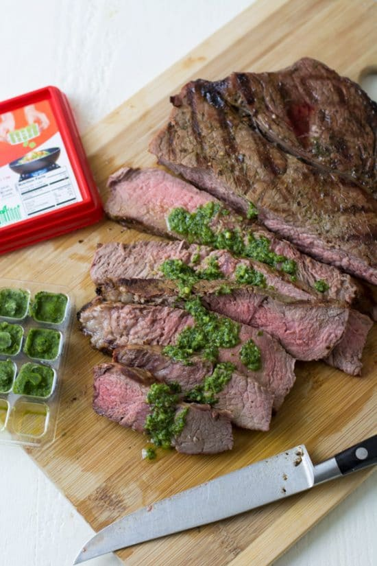 Steak on a cutting board with a basil sauce on top
