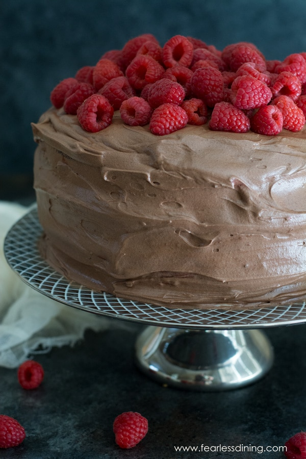 A gluten free chocolate raspberry layer cake on a silver cake stand. The cake is topped with a pile of fresh raspberries.