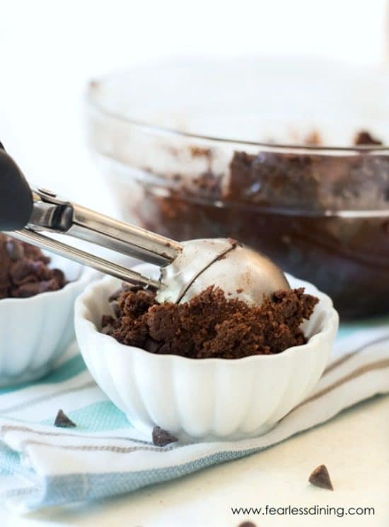 A cookie scoop is filling a white bowl with gluten free chocolate cookie dough