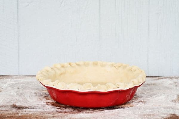a pie crust in a red dish ready to bake