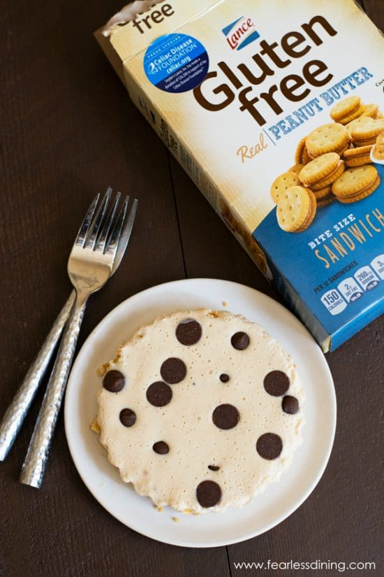 A box of crackers next to a plate with a mini peanut butter pie. The pie is topped with chocolate chips.