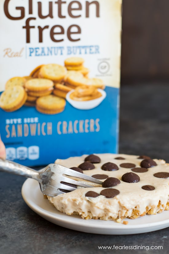 A fork is cutting into a piece of peanut butter pie. A cracker box is in the background.