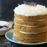 a 5 layer gluten free carrot cake with cream cheese frosting between the layers and on top. Garnished with fresh lavender