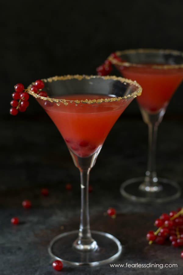 Two martini glasses filled with red currant margaritas. Fresh red currants are draped over the rim of each glass.