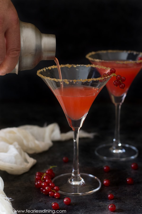 A shaker is pouring the red currant margarita into a tall martini glass.