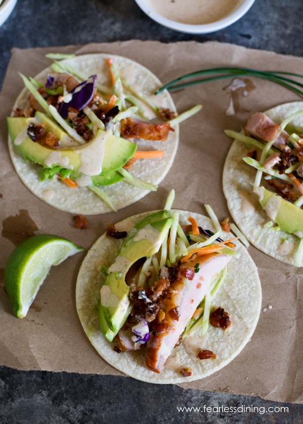 Looking down at three tacos. The tacos are on a brown paper bag. They are topped with avocado and a slice of lime.