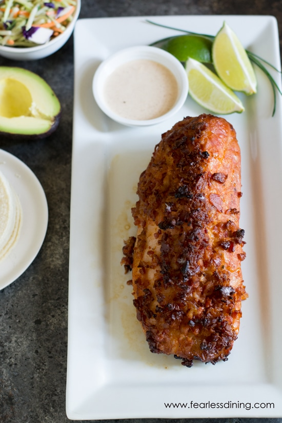 A rectangular white plate with a grilled pork tenderloin on it. Cut limes and a dipping sauce are also on the plate.