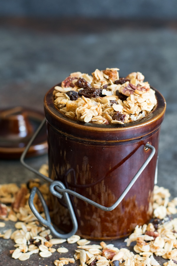 A brown jar of granola with granola spilling onto the table.