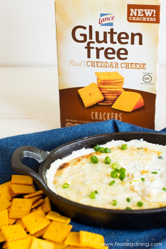 A box of crackers behind a black baking dish filled with cheese dip.