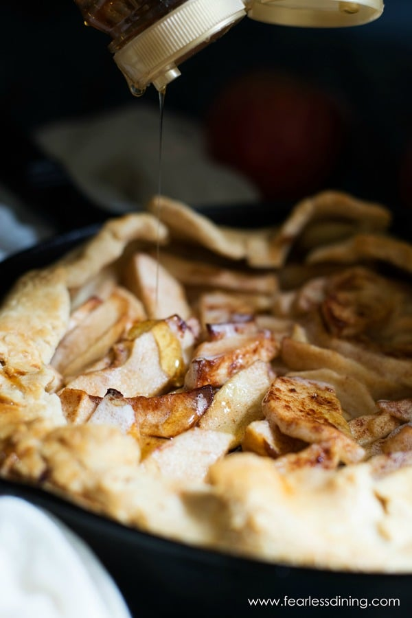 A bottle of honey is above an apple galette. Honey is drizzling out of the bottle onto the galette.