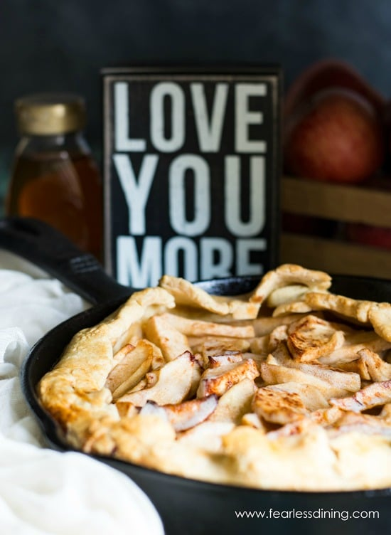 A gluten free honey apple galette in a cast iron skillet. A sign that says Love You More is behind the skillet