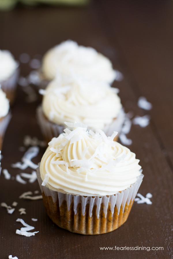 A row of gluten free carrot cupcakes with cream cheese frosting.