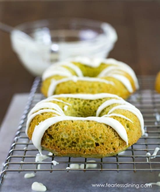 Two matcha green tea donuts with white chocolate drizzle on a cooling rack