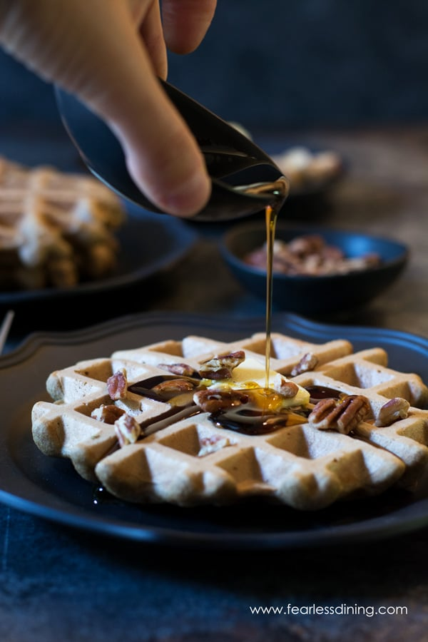 Maple Syrup being poured onto a banana flour waffle. The waffle is topped with butter and pecan halves.
