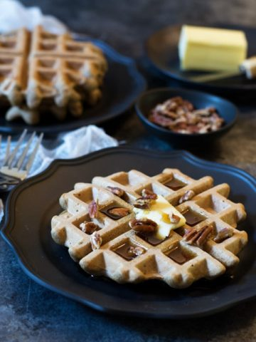 black plate with Banana Flour Waffles garnished with pecans