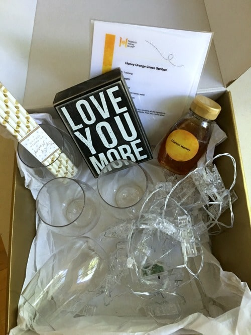 "A gift box with wine glasses, straws, honey, and a sign that says ""love you more"""