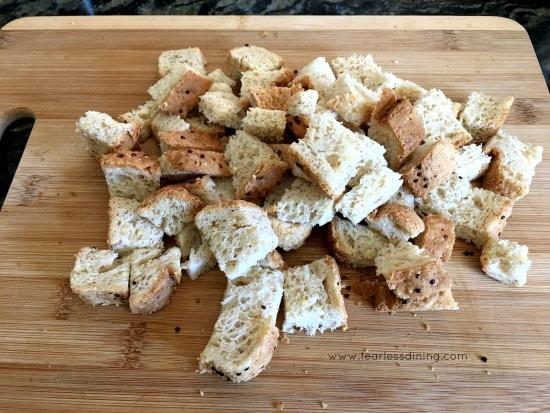 cubed gluten free bread on a wooden cutting board.