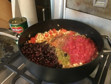 Corn, onion, diced tomatoes and black beans cooking on the stove.