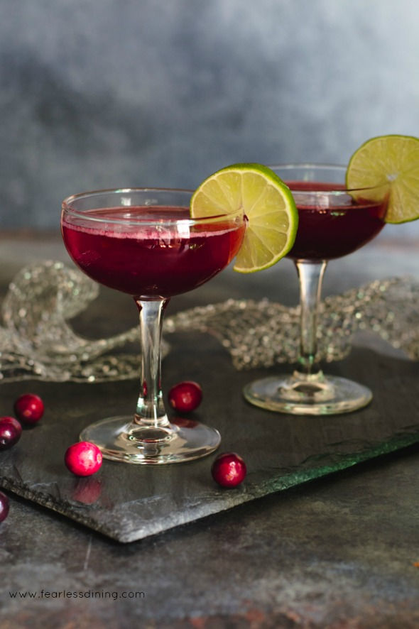 Two glasses of a cranberry rum cocktail on a slate tile. Round lime wedges garnish the glasses.